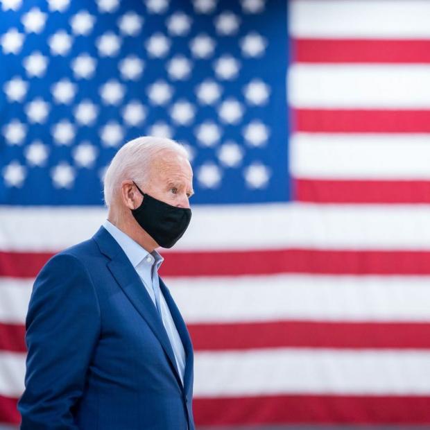 Джо Байден в маске для лица на фоне американского флага