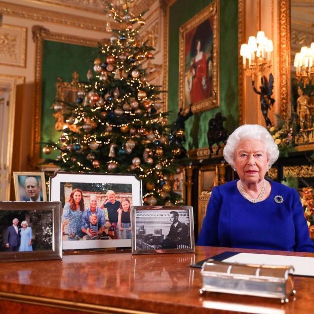 Елизавета II сидит за столом на фоне рождественской елки