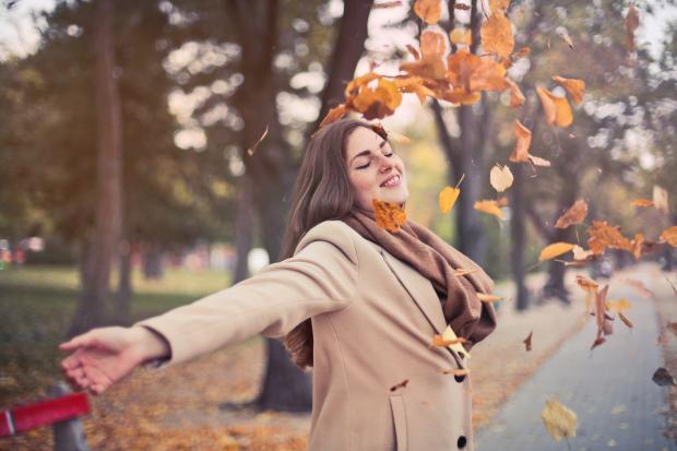 Девушка в бежевом пальто бросает листья в воздух