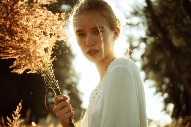 Девушка в белой блузе держит в руках пшеницу