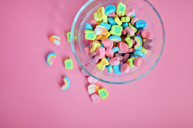 Яркие конфеты в прозрачной мисочке на розовом столе