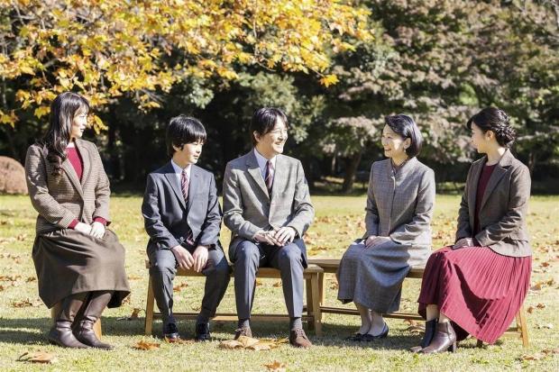 Принц Фухимито с женой и детьми сидит в саду