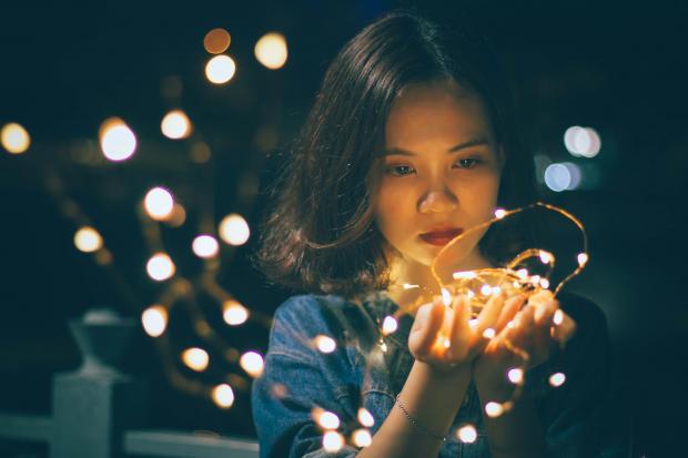 Девушка держит в руках светящуюся гирлянду