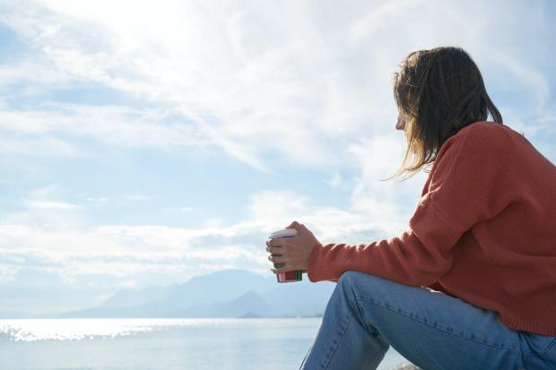 Девушка в красной кофте и синих джинсах сидит на природе с чашкой в руках