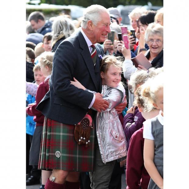 Принц Чарльз в килте обнимается с маленькой девочкой