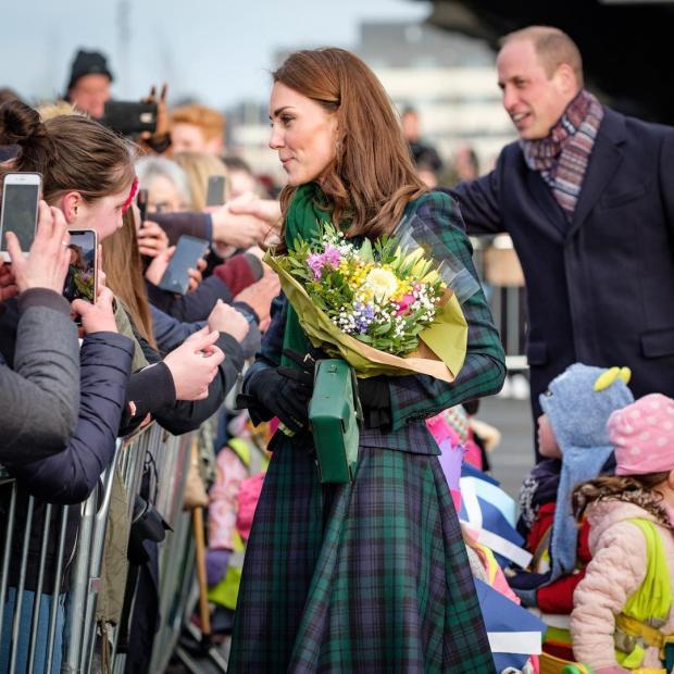 Кейт Миддлтон в клетчатом пальто с цветами в руках общается с фанатами