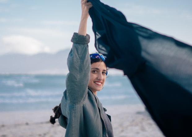 Девушка в серой куртке  держит темный шарф над головой