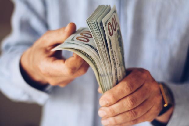 пачка долларов у мужчины в руках