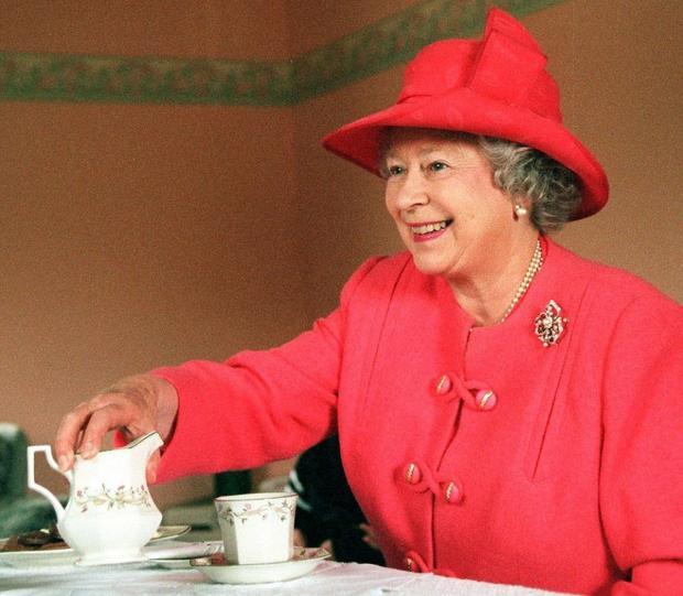 Елизавета II в красном наряде пьет чай