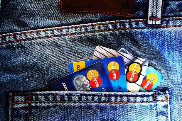 банковские карты лежат в заднем кармане джинсовых брюк