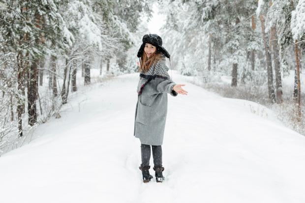 девушка прогуливается по заснеженному парку