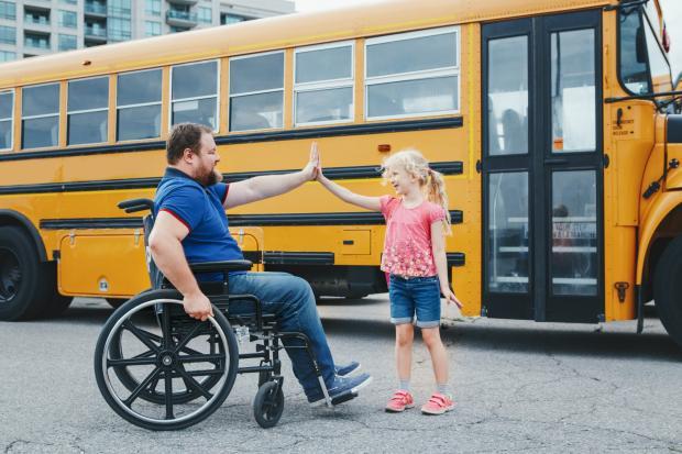 мужчина в инвалидной коляске и его дочь