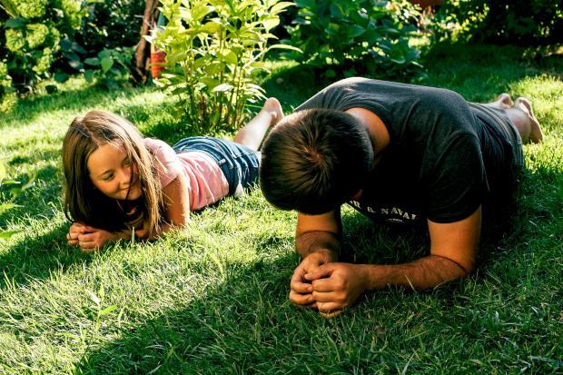 папа с дочкой лежат на траве