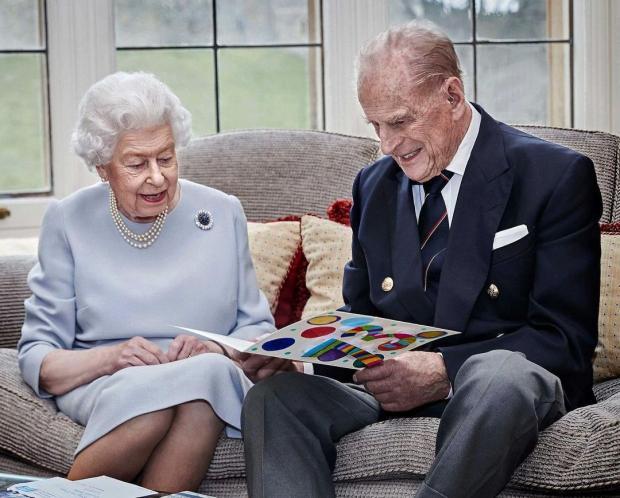Елизавета II и Принц Филипп смотрят открытку, подаренную внуком