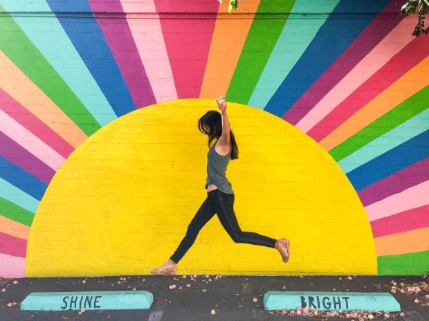 девушка прыгает на фоне радужной стены
