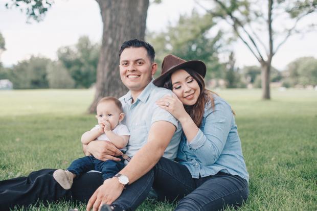 семья отдыхает на газоне под деревом