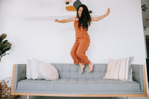 девушка прыгает на диване