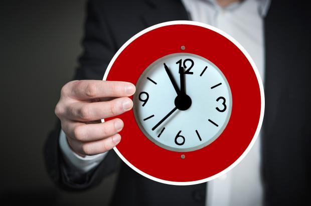 мужчина держит в руке красный циферблат часов