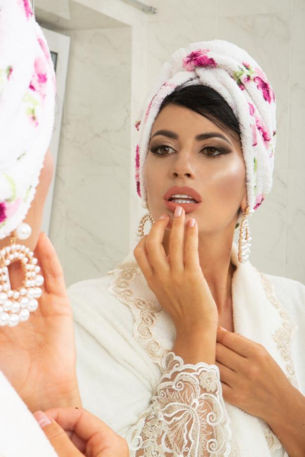 красивая девушка в халате и полотенце смотрится в зеркало