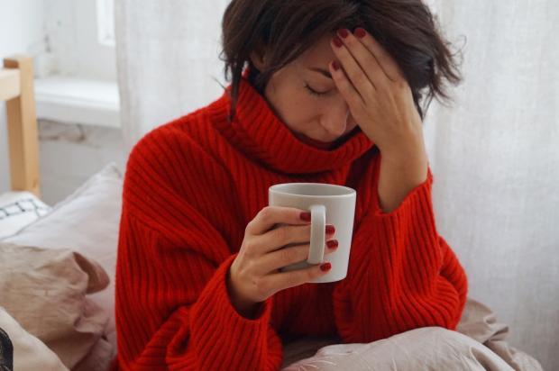женщина в красном свитере пьет чай во время простуды