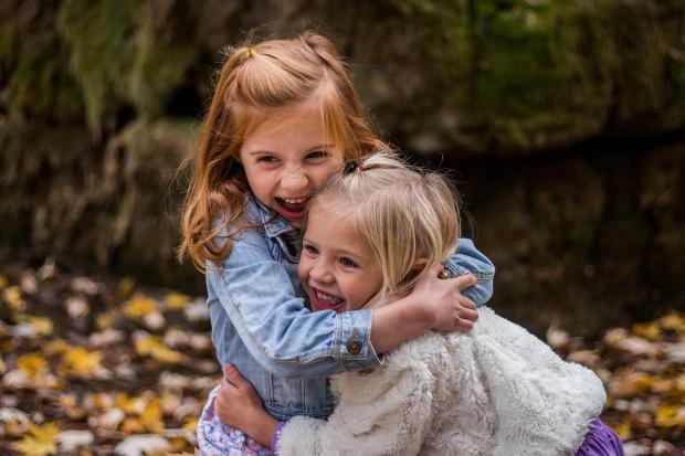 две маленьких девочки обнимаются и весело смеются