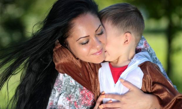 черноволосая женщина с распущенными волосами обнимает маленького мальчика