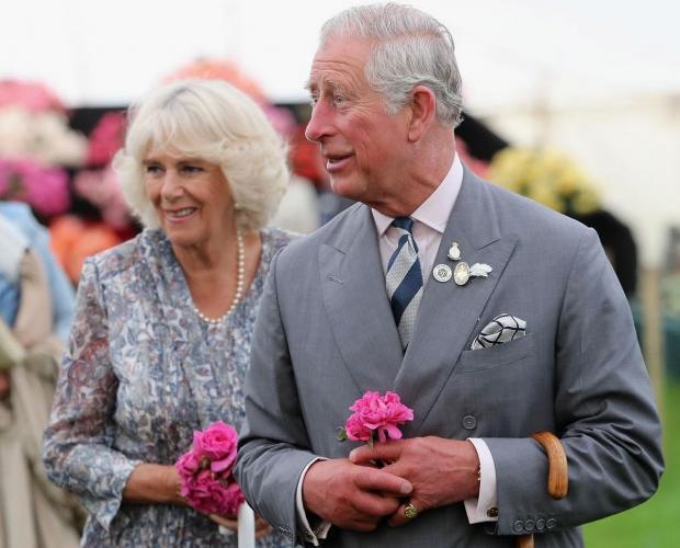 Принц Чарльз и Камилла идут мимо фанатов с цветами в руках