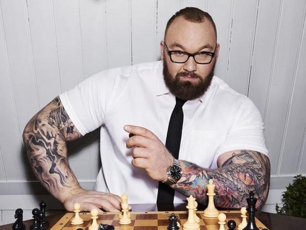 Хафтор позирует возле шахмат в рубашке