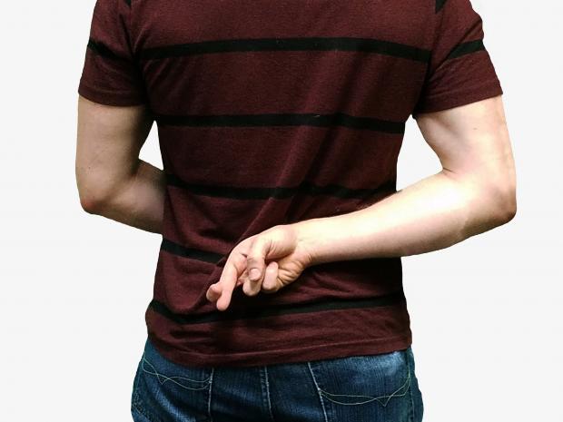 молодой человек держит скрещенными пальцы за спиной