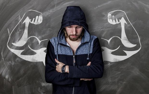 молодой человек стоит спиной к доске, где нарисованы бицепсы