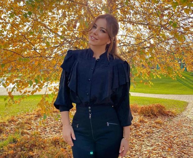 Ани Лорак в черном костюме на фоне осеннего дерева