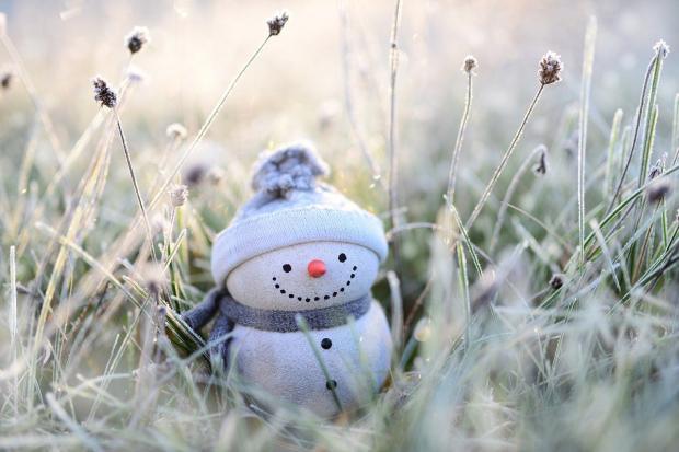 игрушечный снеговик в вязаной шапочке стоит среди заснеженной травы