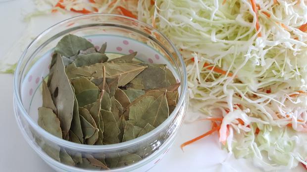 лавровый лист в стеклянной плошке рядом с нарезанной капустой