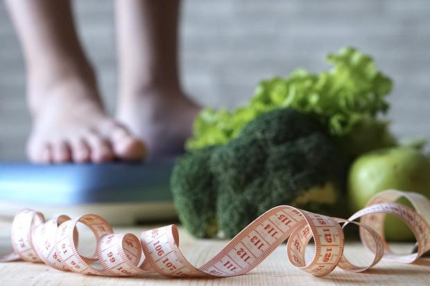 человек на весах, овощи и сантиметр