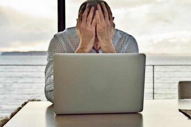 мужчина закрыл лицо перед ноутбуком