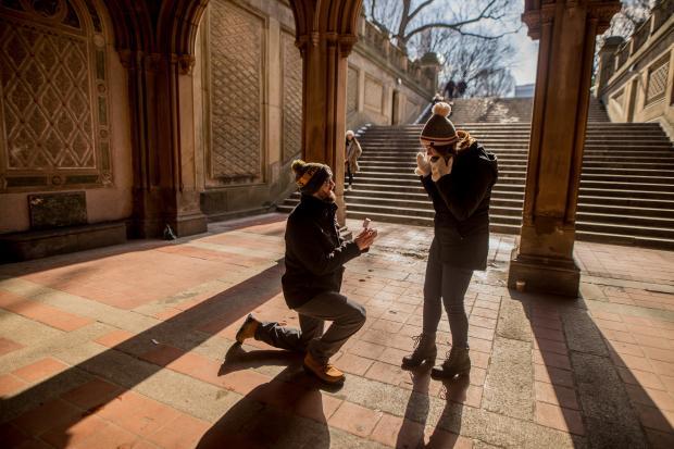 Молодой человек в теплой одежде и шапке делает предложение руки и сердца девушке