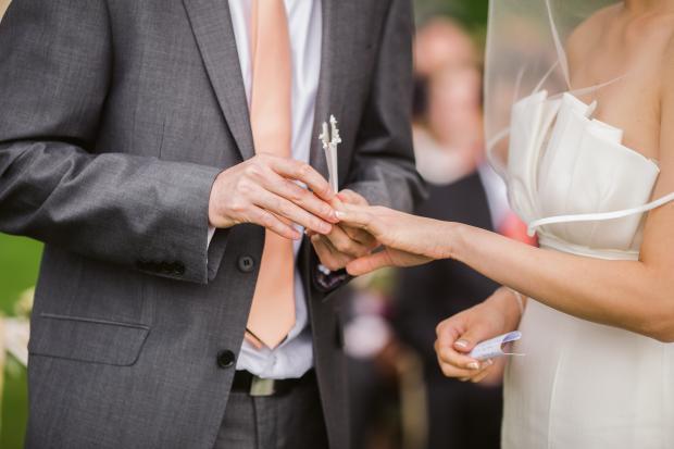 Мужчина в костюме надевает красивое кольцо на палец женщины в белом платье