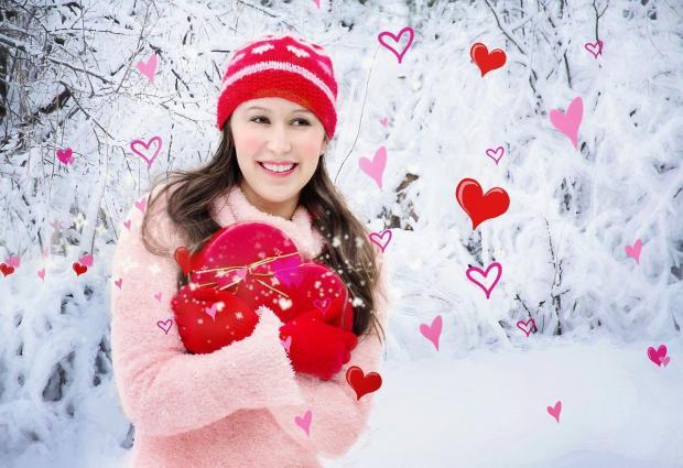 девушка улыбается в окружении  красных сердечек