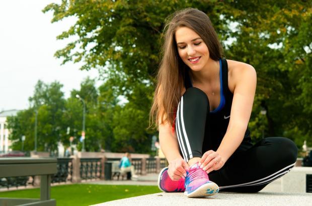 Длинноволосая девушка в п=спортивном костюме завязывает обувь