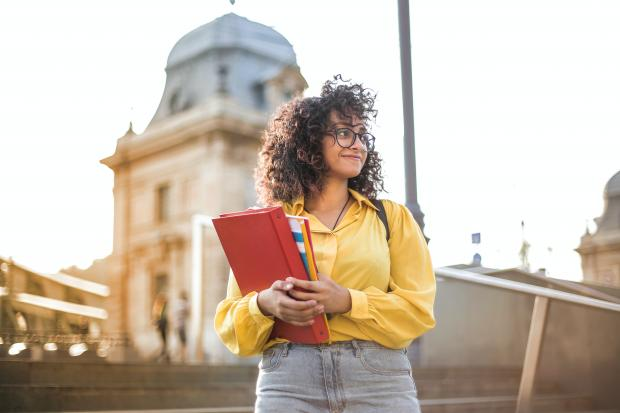 Кучерявая девушка в желтой блузе с красной папкой в руках
