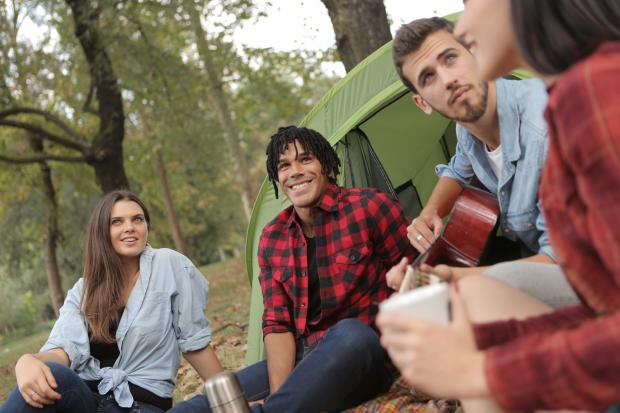 Компания молодых людей сидят на земле возле палатки