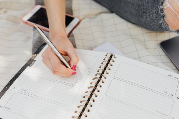 девушка пишет ручкой в блокноте