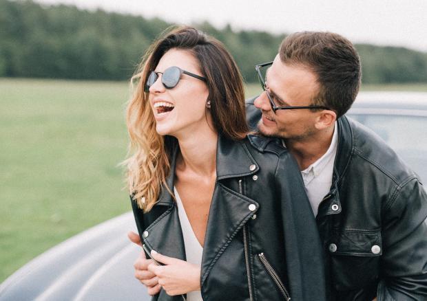 Молодые парень и девушка в кожаных куртках обнимаются около машины
