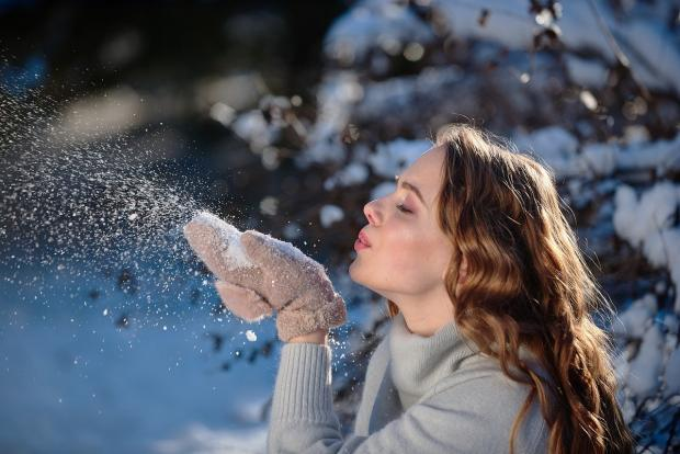 девушка дует на снег в ладошках