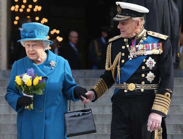 Елизавета II в синем пальто, а Принц Филипп в военной форме