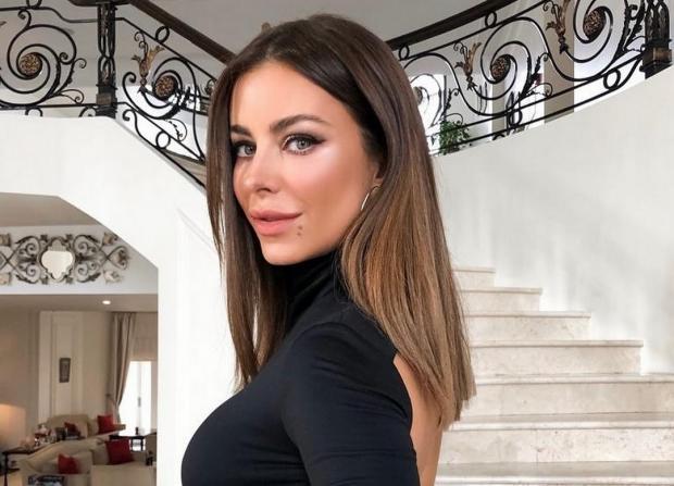 Ани Лорак в черном гольфе стоит на лестнице