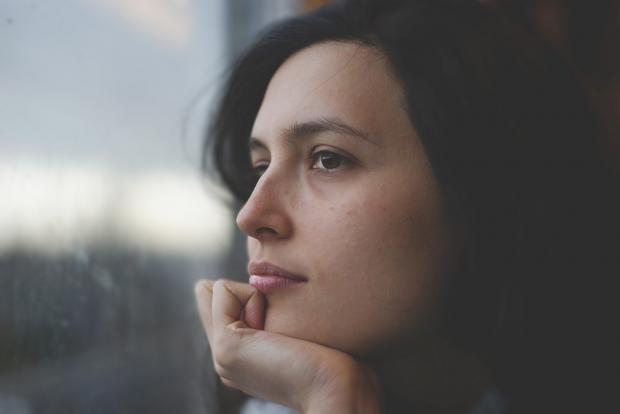девушка задумчиво смотрит в окно