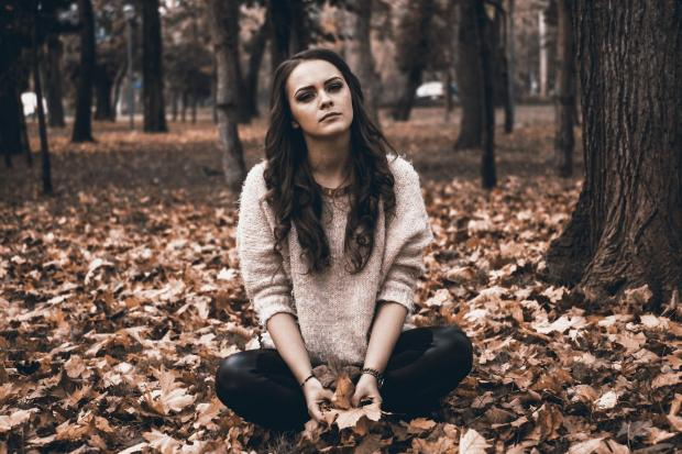 девушка задумчиво сидит на осенней листве
