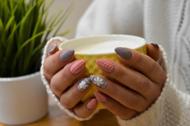 девушка с красивым маникюром в белом свитере держит в руках желтую чашку с молоком