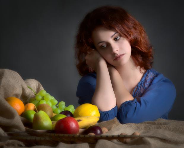 девушка с грусть смотрит на фрукты